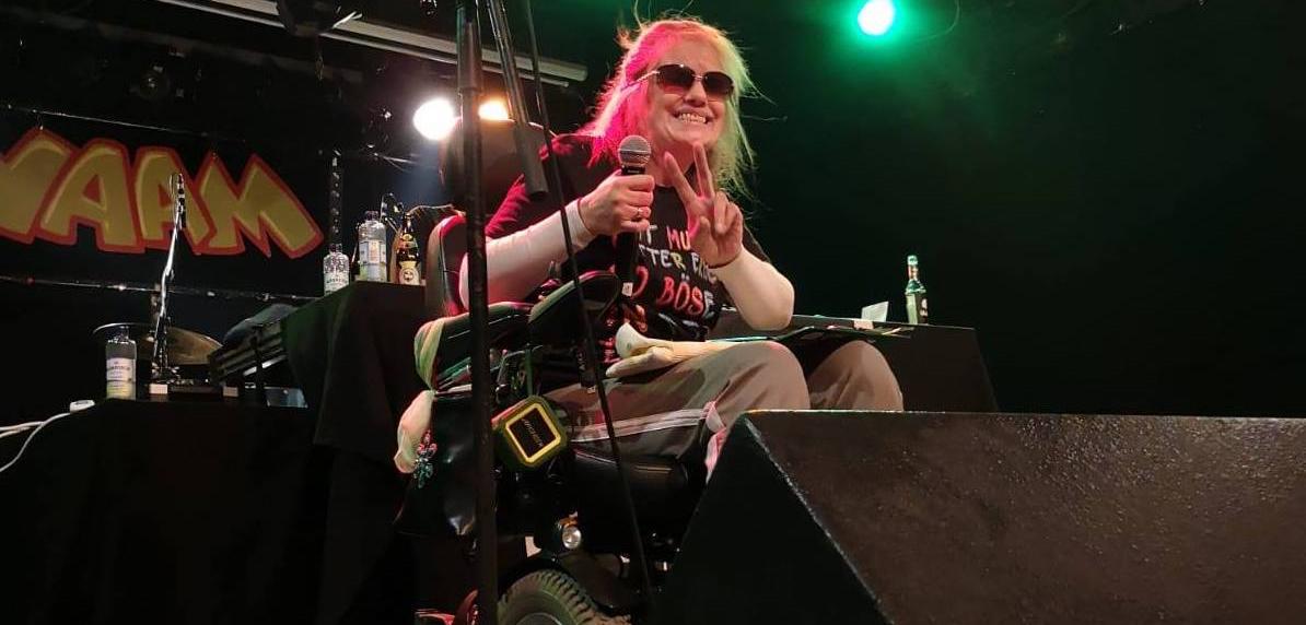 """STR8MUDDI / DAT MUDDI live auf der Bühne im YAAM, mit Sonnenbrille guckt sie in die Kamera und macht ein """"Victory"""" Zeichen"""