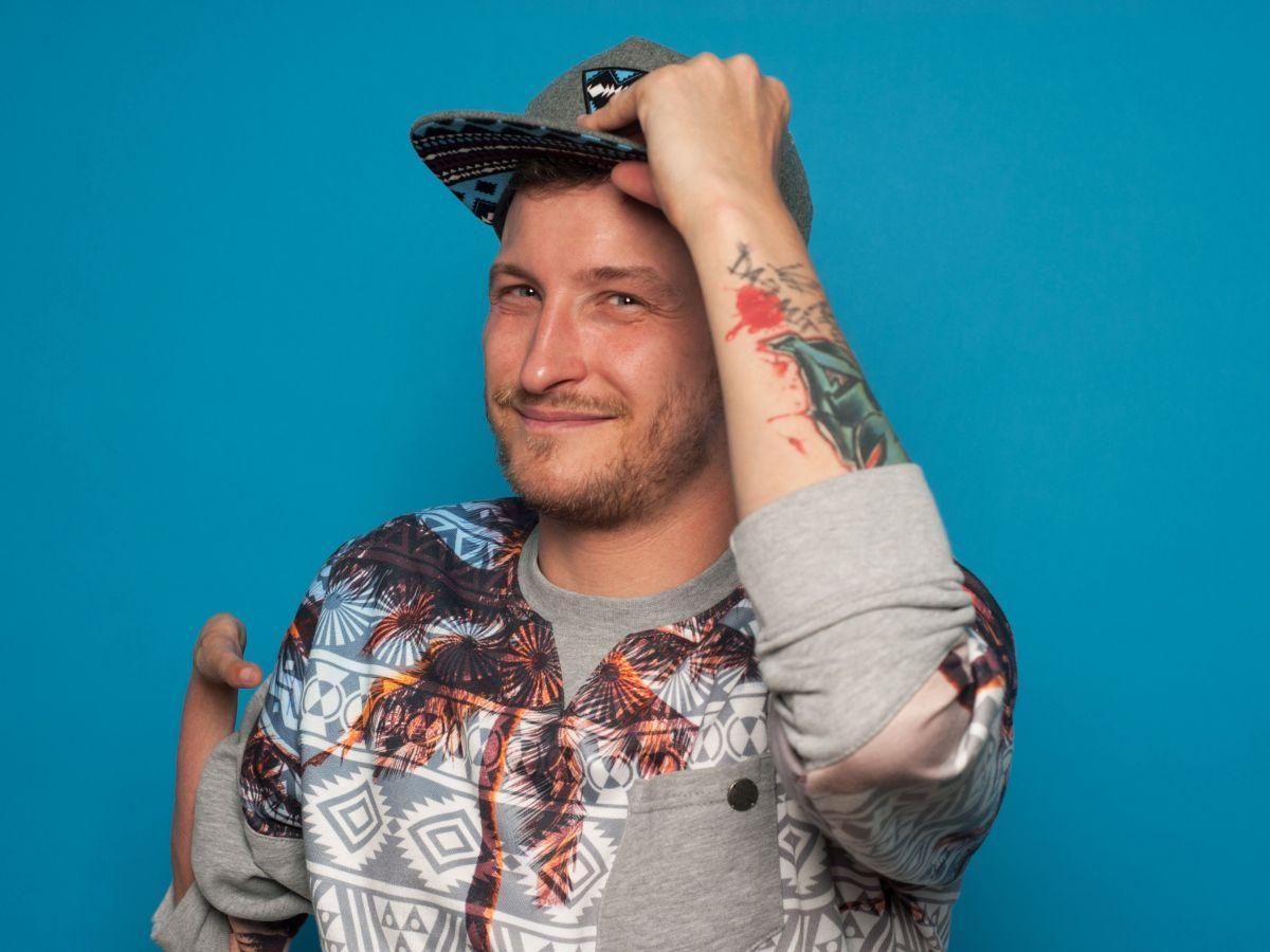 Graf Fidi freundlich in die Kamera blickend, mit Basecap und Tattoo