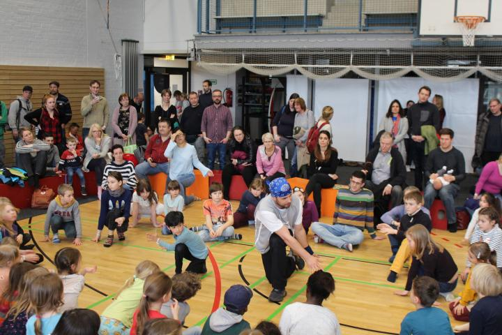 Zwölf Kinder zeigen eine Tanzdarbietung in einer Sporthalle, zusammen mit einem Erwachsenen, rundherum steht und sitzt ein bunt gemischtes Publikum
