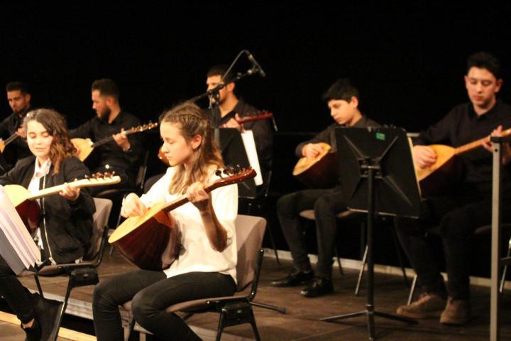 Sechs Jungendliche beim Musizieren mit Saiteninstrumenten auf der Bühne, alle schwart weiß gekleidet