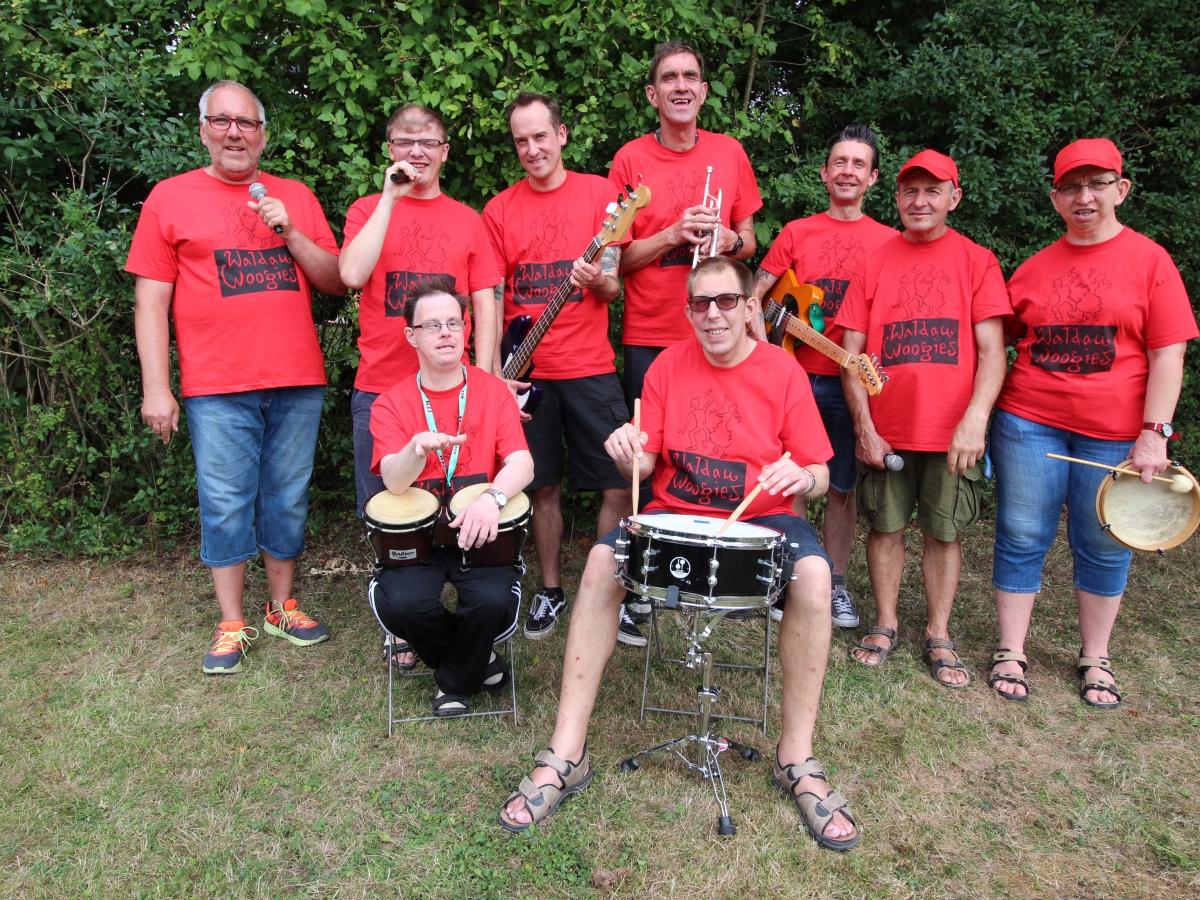 Die neun Mitglieder der Band WALDAU WOOGIES mit roten T-Shirts und Ihren Instrumenten auf einer Wiese vor einer Hecke, 7 Mitglieder stehend, zwei Mitglieder mit Bongos und Schalgzeug sitzend