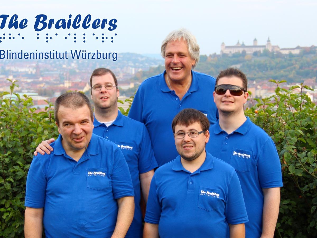 """Foto von den fünf Mitgliedern der Band """"The Braillers"""" in bleuen Band-T-Shirts, vor einer niedrigen Hecke, dahinter im Hintergrund das schöne Panorama von Würzburg, samt Burg, dazu das Logo der Band inklusive Schriftzug """"Blindeninstitut Würzburg"""""""