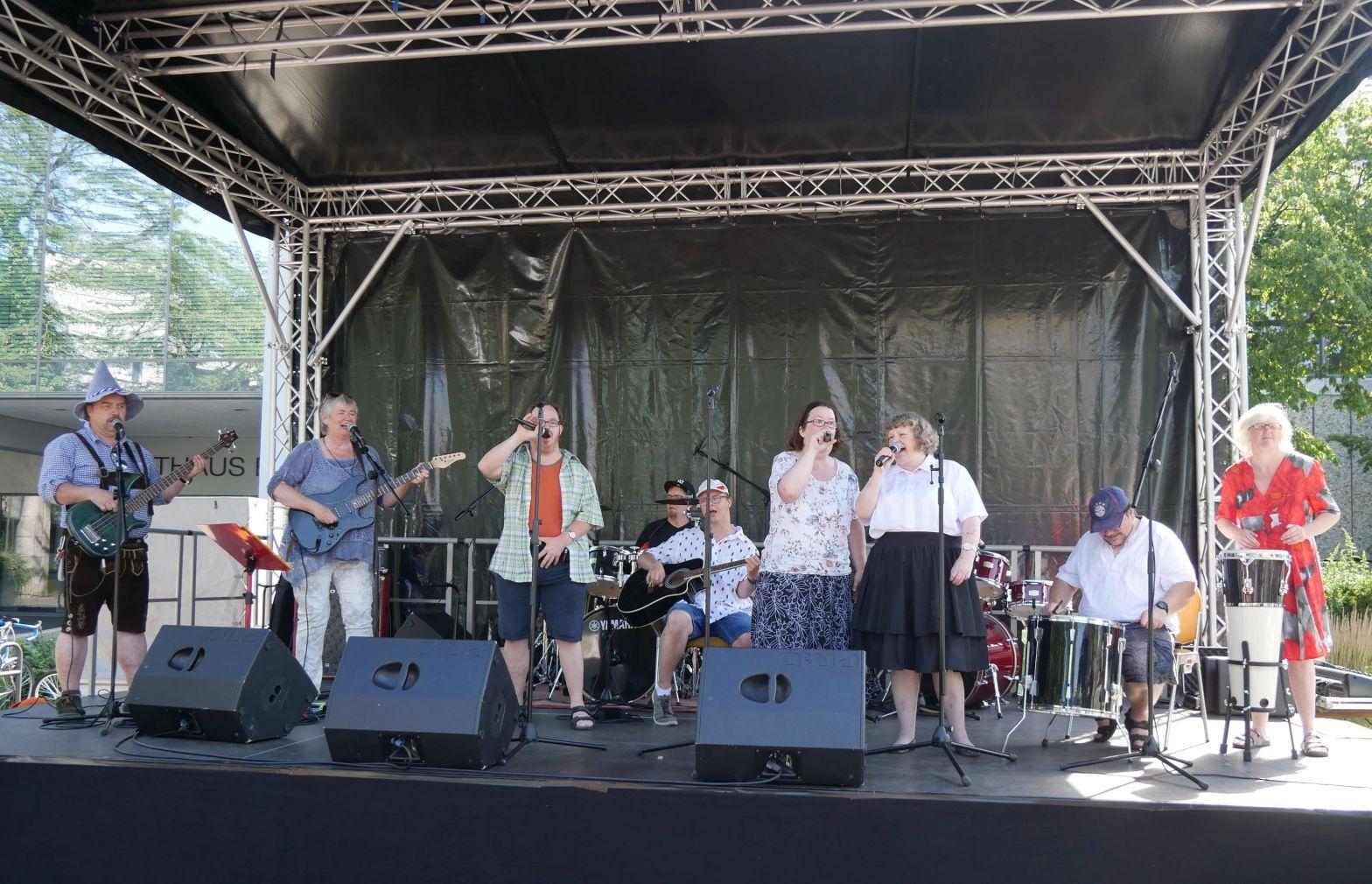 Neun Mitglieder der Band Honey Sweet & The 7 Ups auf einer Freilichtbühne live beim Auftritt