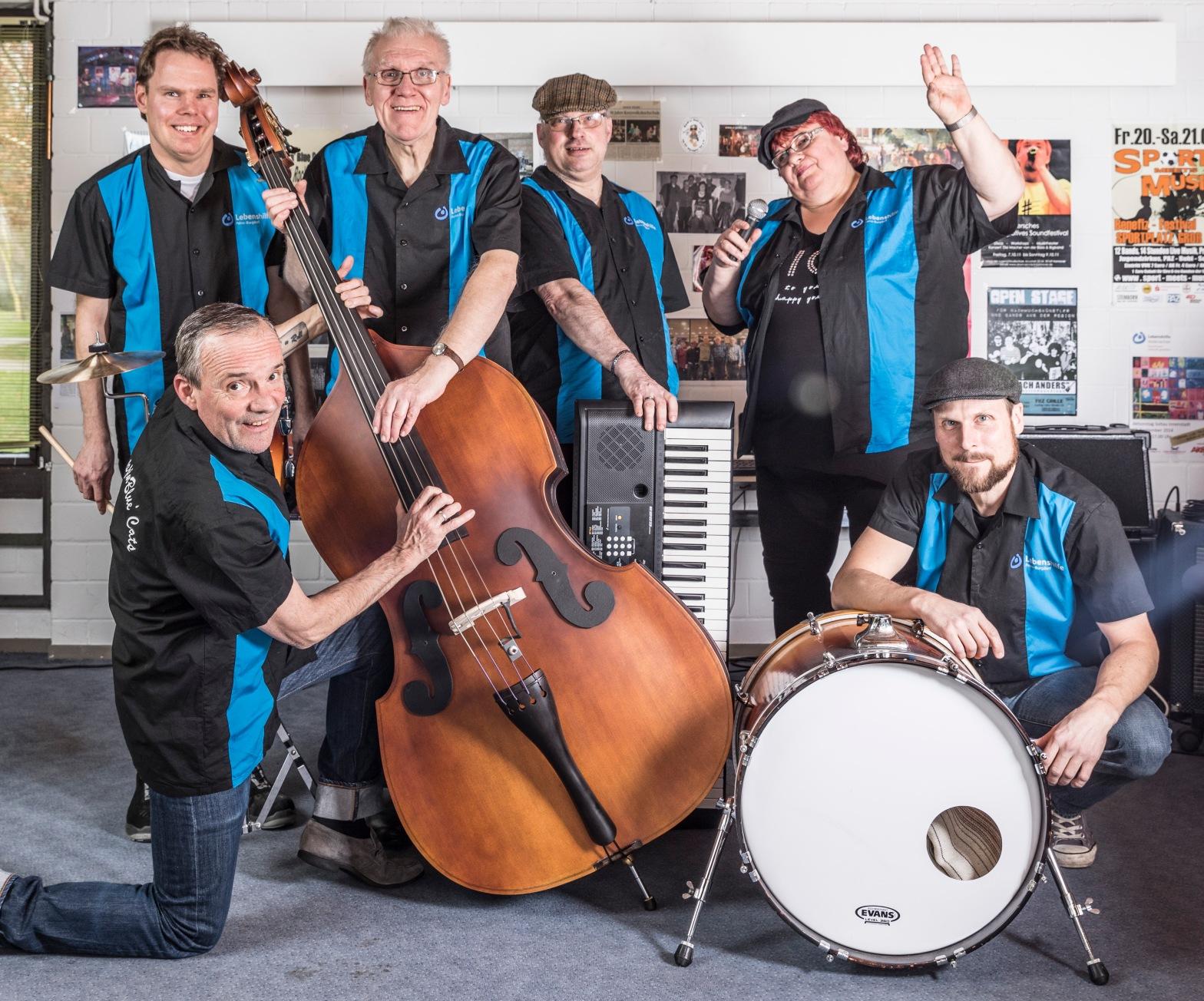 Sechs Mitglieder der Band Boppin´Blue Cats mit einem großen Bass, einem Keyboard und einer Basstrommel, gut gelaunt und alle mit den gleichen schwarz blauen Hemden