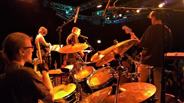 Die Band The Way live auf der Bühne, von hinter dem Schlagzeug fotografiert