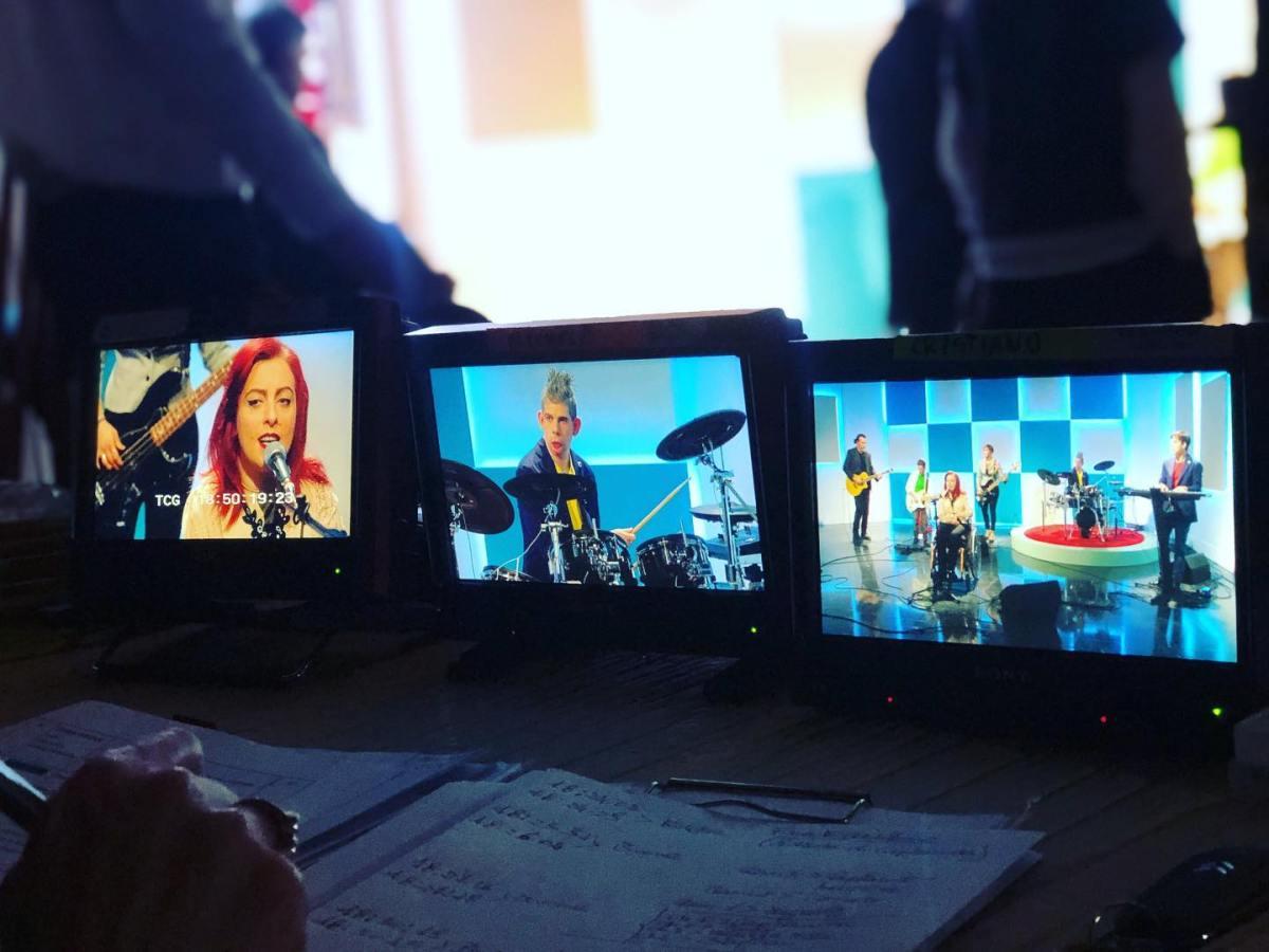Die Band auf drei Monitoren beim Auftritt im Fernsehen