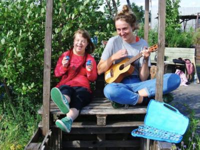 Mädchen und Frau mit Ukulele musizieren sehr fröhlich im Grünen