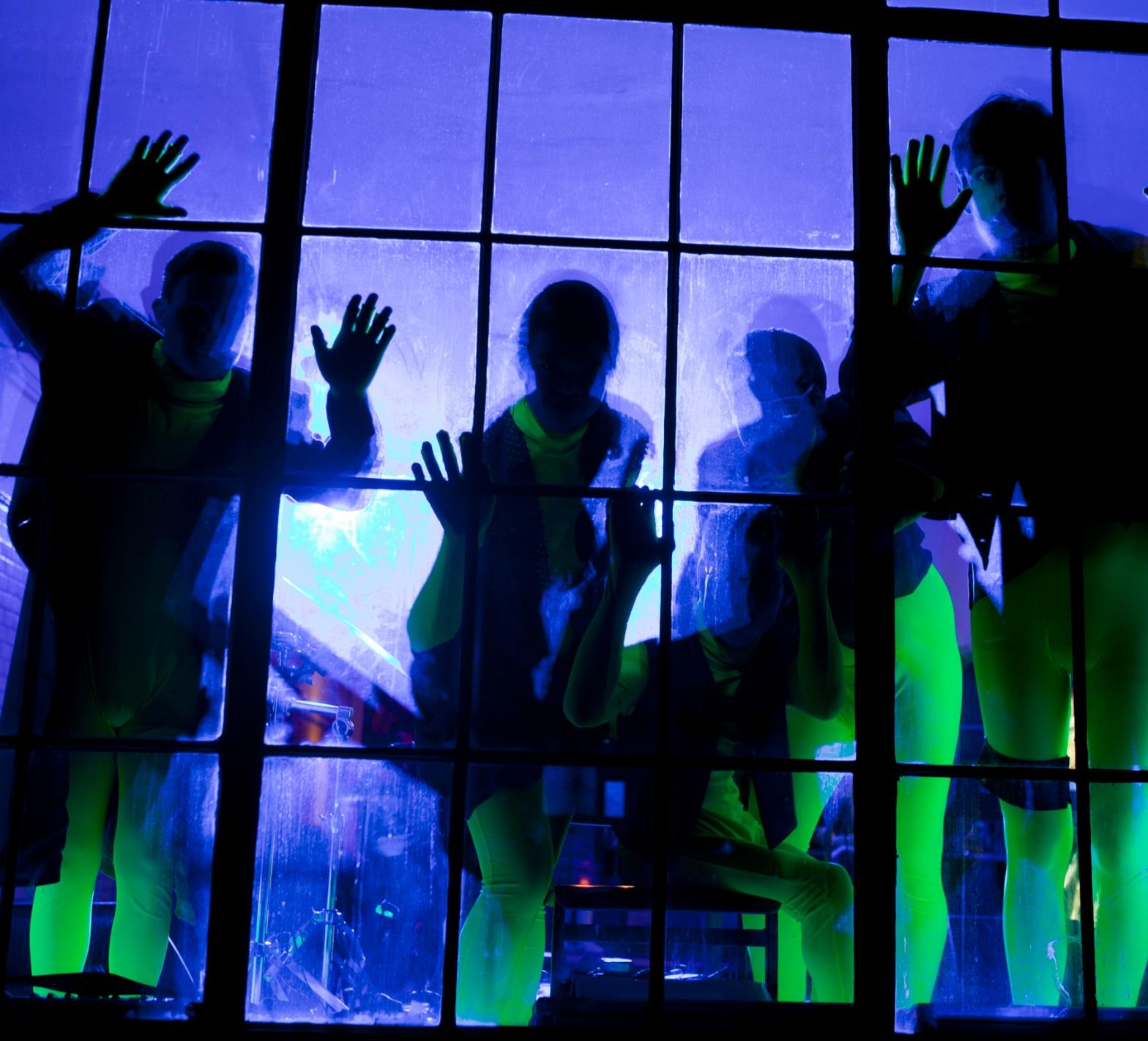 Fünf Menschen als Schatten hinter einer blau erleuchteten Scheibe mit gelben Neoneffekten