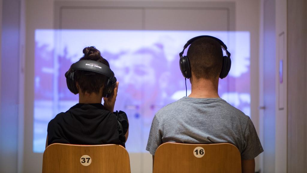 Ein Mann und eine Frau mit Kopfhörern, von hinten vor einer Videoprojektion.