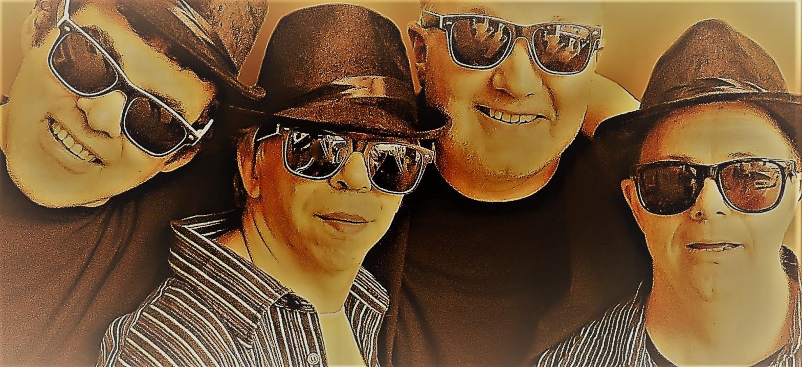 Vier coole Typen mit Sonnenbrillen und Hüten gucken freundlich in die Kamera.