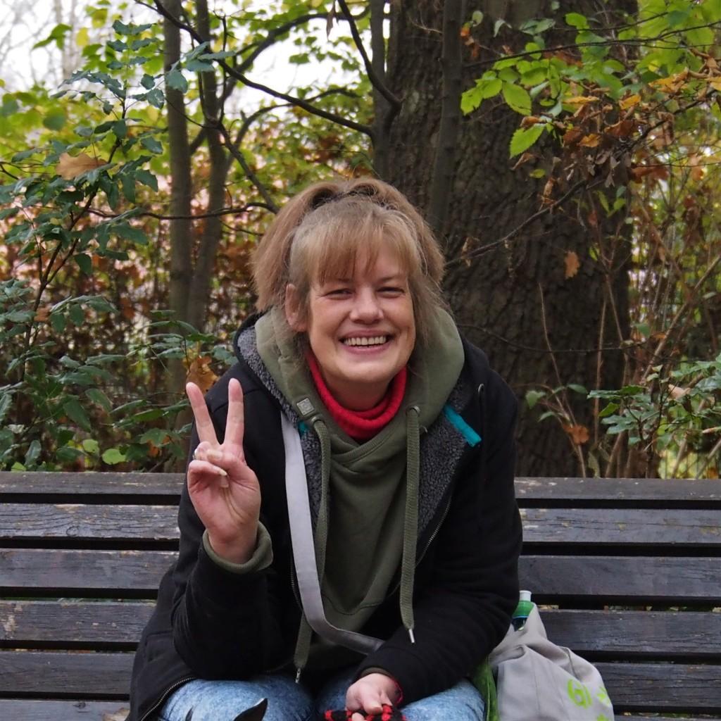 Claudia auf der Parkbank, lächelt in die Kamera und macht das Vicotry Zeichen mit ihrer Hand