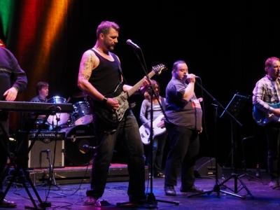 Sechs Mitglieder der Band Soulhossas live auf der Bühne mit Gitarre, Bass, Keyboard und Schlagzeug