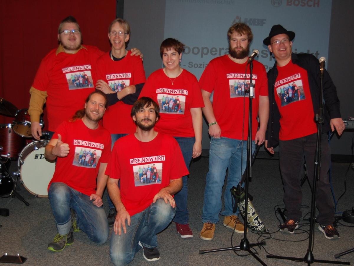 Sieben Mitglieder der Band Brennwert, alle im orten Band T-Shirt, posieren für ein Gruppenfoto auf einer Bühne (innen)
