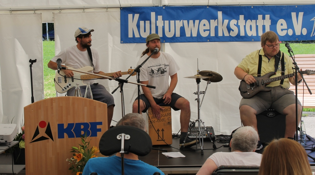 Drei Mitglieder der Band Brennwert, live beim Auftritt auf einer Freilichtbühne, mit E-Gitarre, E-Bass und Cajon. Der Cajonspieler singt in ein Mikrophon.
