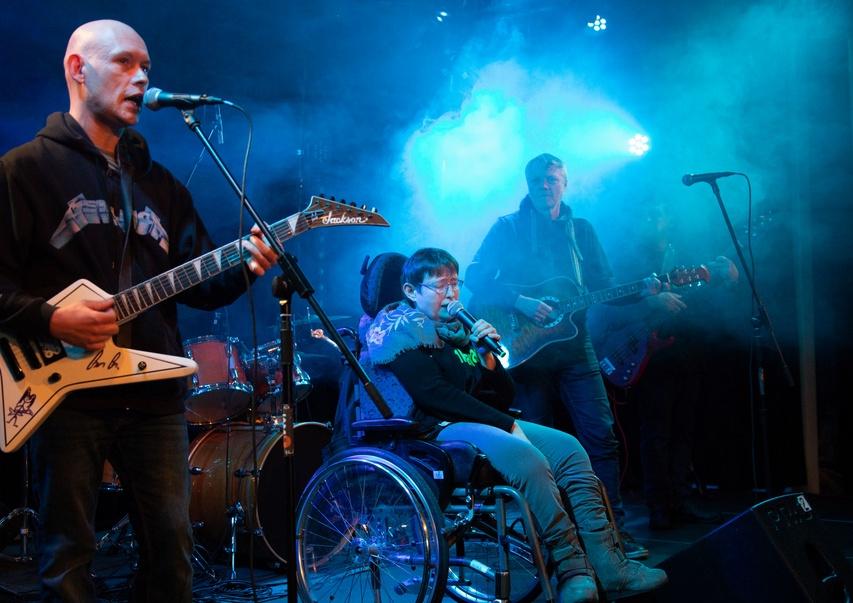 Drei Mitglieder der Band Vollkaracho live beim Auftritt auf der Bühne mit E-Gitarre, Akustik-Gitarre, Schlagzeug und Rollstuhl, dazu viel Bühnennebel