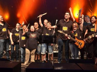 11 Mitglieder der Band PowerPack jubeln nach einem Auftritt auf der Bühne