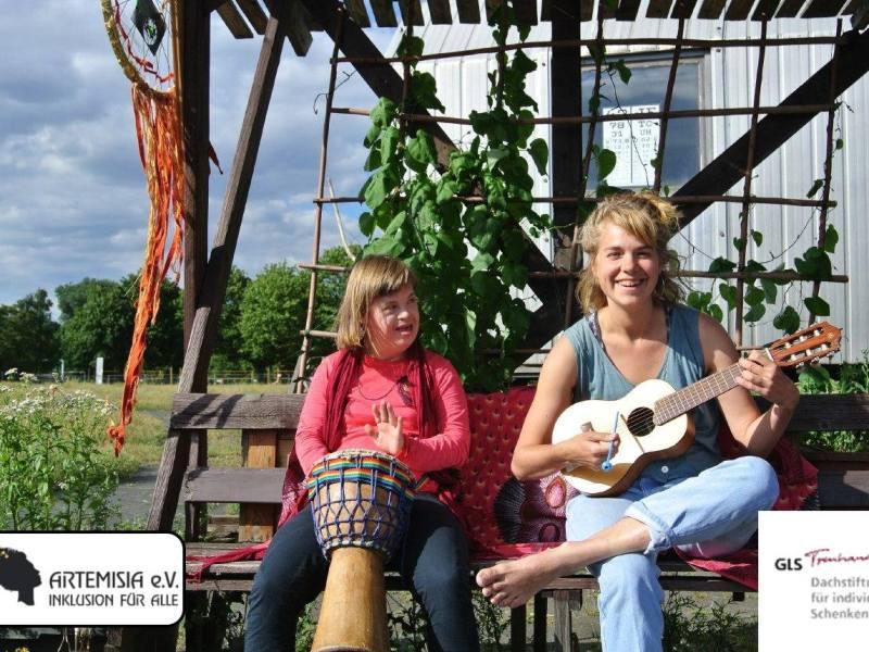 Zwei Frauen sitzen im Grünen auf einer Bank und musizieren gut gelaunt mit einer Ukulele und einer Bongo