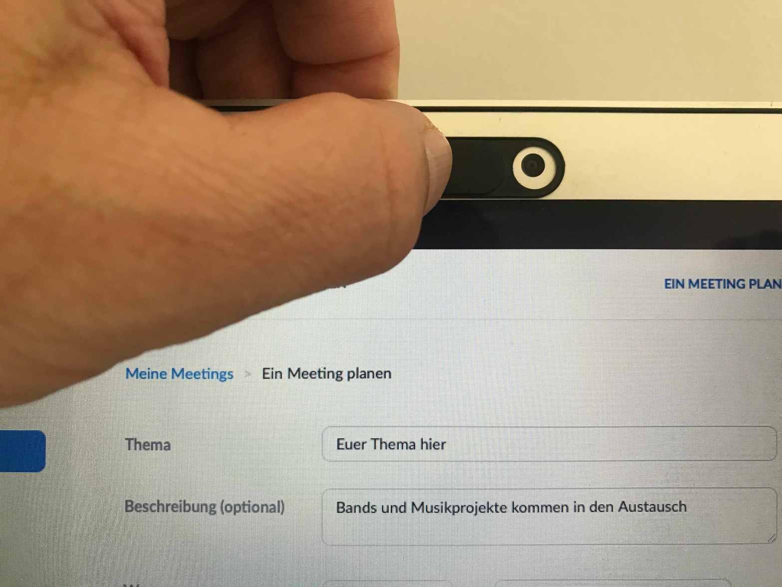 """Eine Hand öffnet eine Webcam an einem Laptop, darunter ist zu lesen: """"Ein Meeting planen"""" und """"Euer Thema hier - Bands und Musikprojekte kommen in den Austausch"""""""