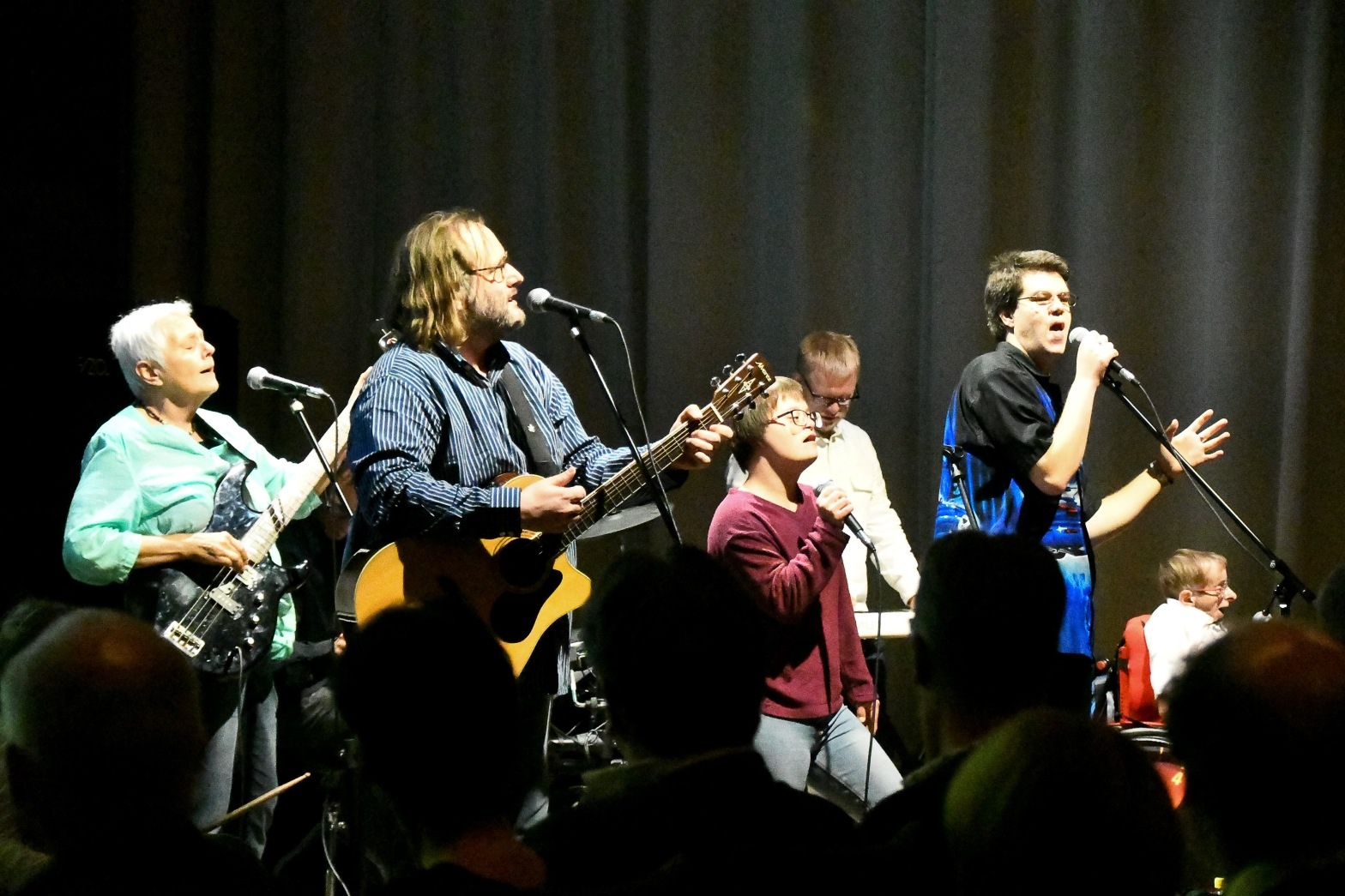 Sechs Musizierende auf einer Bühne, von links nach rechts eine Musikerin mit E-Bass, ein Musiker mit Akustikgitarre, eine Sängerin, ein Keyboarder und zwei Sänger. im Vordergrund Schatten von sitzendem Publikum, im Hintergrund ein grauer Vorhang