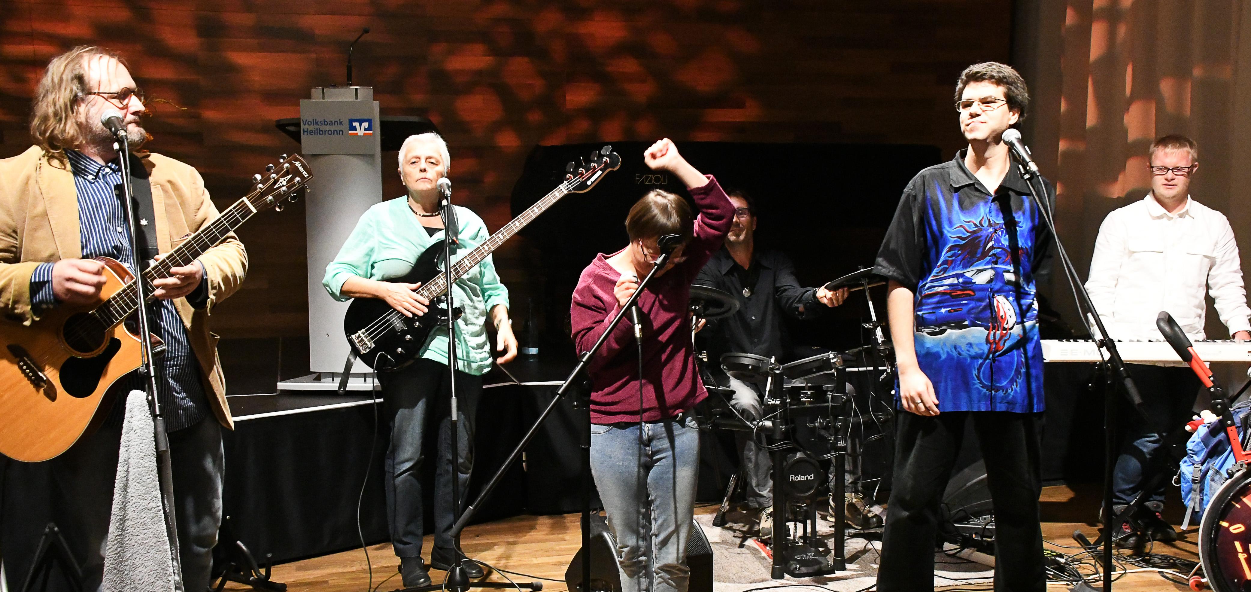 Sechs Musiker auf einer Bühne, von Vorne fotografie, von links nach rechts: Ein Musiker mit Akustikgitarre, eine Musikerin mit E-Bass, eine Sängerin mit erhobener Hand, ein Schlagzeuger im Hintergrund, ein Sänger und ein Keyborder
